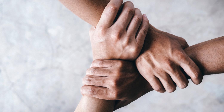 Arme und Hände, die sich gemeinsam im Bild festhalten.
