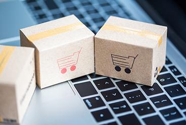 Pakete mit Warenkorb-Aufdruck auf einer Mac-Tastatur